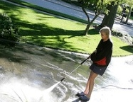 Person washing a driveway with power washer