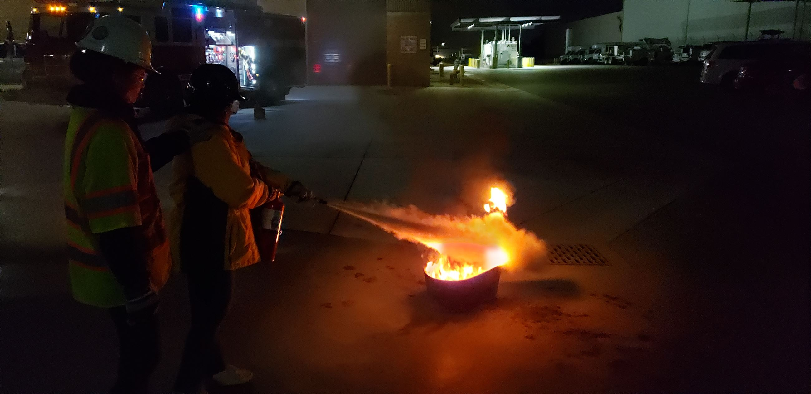 Two CERT members putting out a fire with a fire extinguisher
