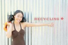 Woman pointing to a recycling sign